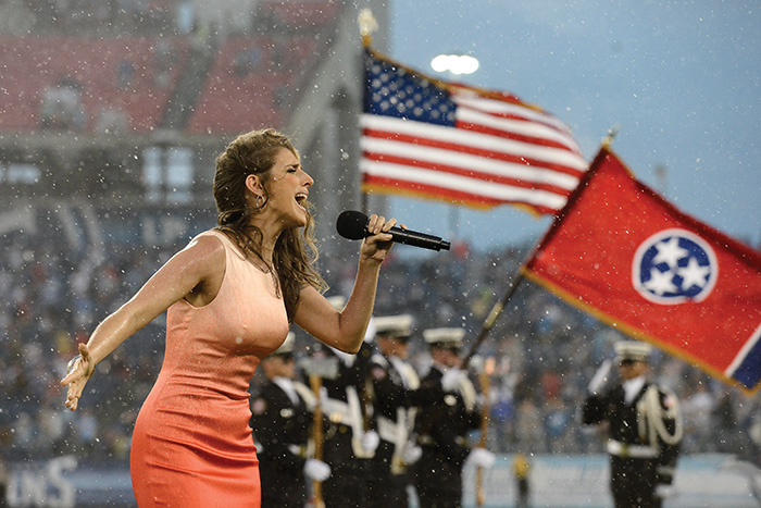 Janine Stange, of Long Island, NY, performs the national anthem before a preseason NFL football game between the Minnesota Vikings and the Tennessee Titans Thursday, Aug. 28, 2014, in Nashville, Tenn. The performance completed Stange's mission of singing the anthem in all 50 states. (AP Photo/Mark Zaleski)