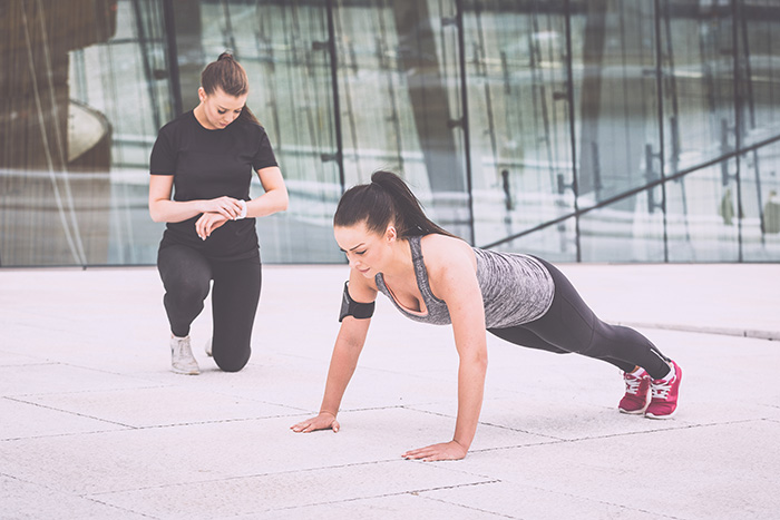 Woman doing push-ups exercises with her personal trainer in a modern urban context. She are wearing gray and black sportswear and a phone holder, the trainer look at watch and incite her